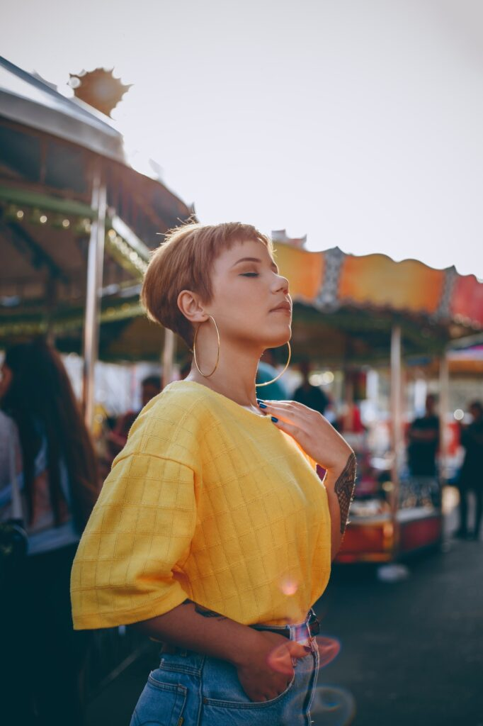 Girl In Yellow Top & Hoop Earrings At Funfair   5 Ways To Wear Earrings To Help Them Be More Flattering   Fashion & Style   Elle Blonde Luxury Lifestyle Destination Blog