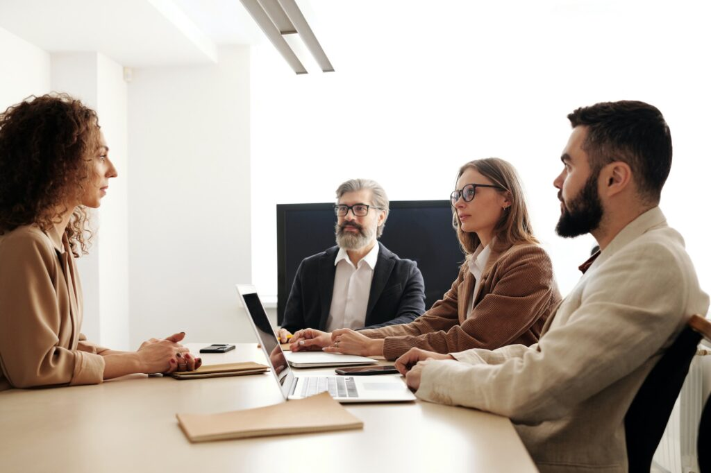 Two men and two women sitting at a table | What Do You Need To Be An HR Consultant? | Business & Education | Elle Blonde Luxury Lifestyle Destination Blog